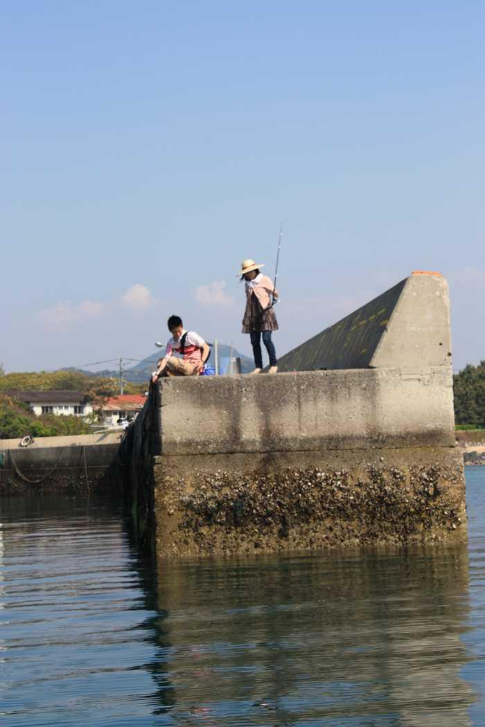 遊覧船の中から見た防波堤の釣り人