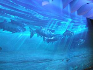 サーモンロードの壁に浮かび上がるブラックライトに照らされた絵