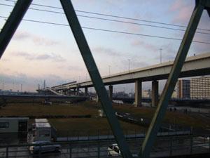 荒川を渡るE217系。車窓には夕暮れ時の首都高C2、葛飾ハープ橋が…。