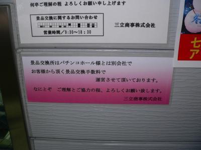 写真キャプション=手数料の説明ポスターの下に添付された景品交換会社の注意書き