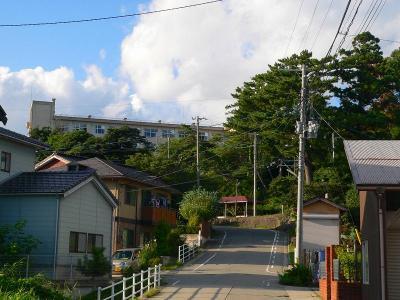 写真キャプション=坂の下から見た佐渡高校の遠景